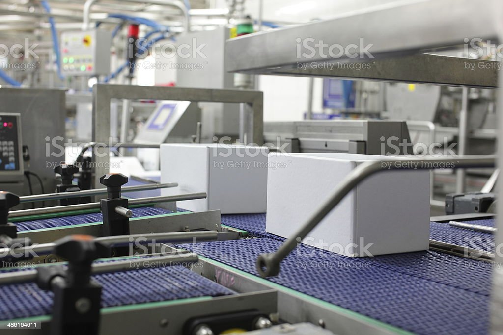 Cardboard boxes on conveyor belts in plant stock photo
