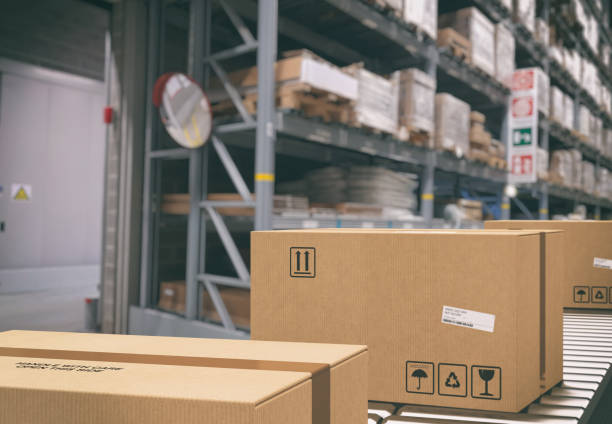 Cardboard boxes on conveyor rollers inside a warehouse ready to be shipped by courier for distribution - foto stock