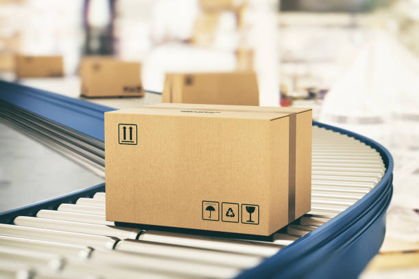 Cardboard boxes on conveyor rollers ready to be shipped by courier for distribution stock photo