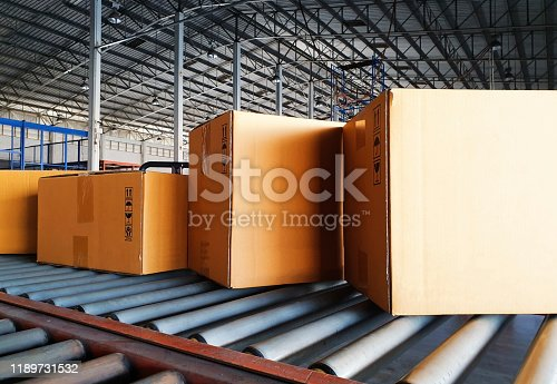 Cardboard boxes or packaging product sorting on conveyor belt at distribution warehouse.