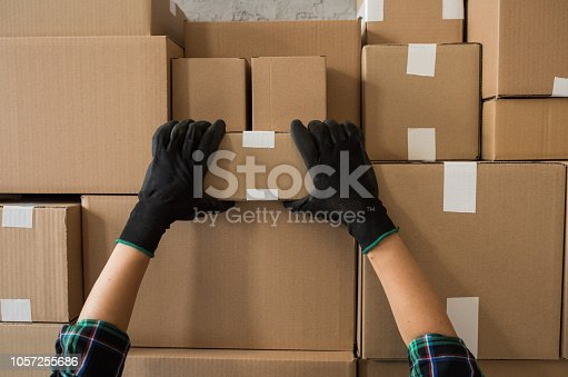 Cardboard boxes stocked by the wall in warehouse. Ready for delivery. Delivery person picking one of boxes.
