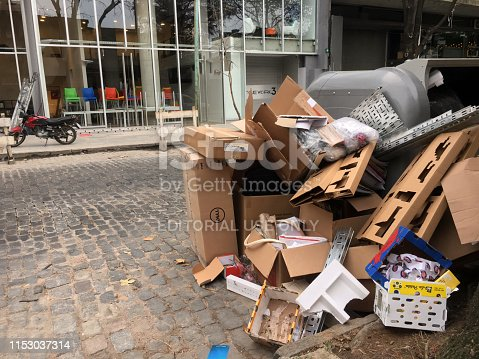 Buenos Aires, Argentina - May 25, 2019: Lots of cardboard boxes stacked next to plastic industrial garbage bin in the street. People leave them outside the container so the 'cartoneros', people that collect them to take them to recycling facilities and getting some money for their job, would grab them