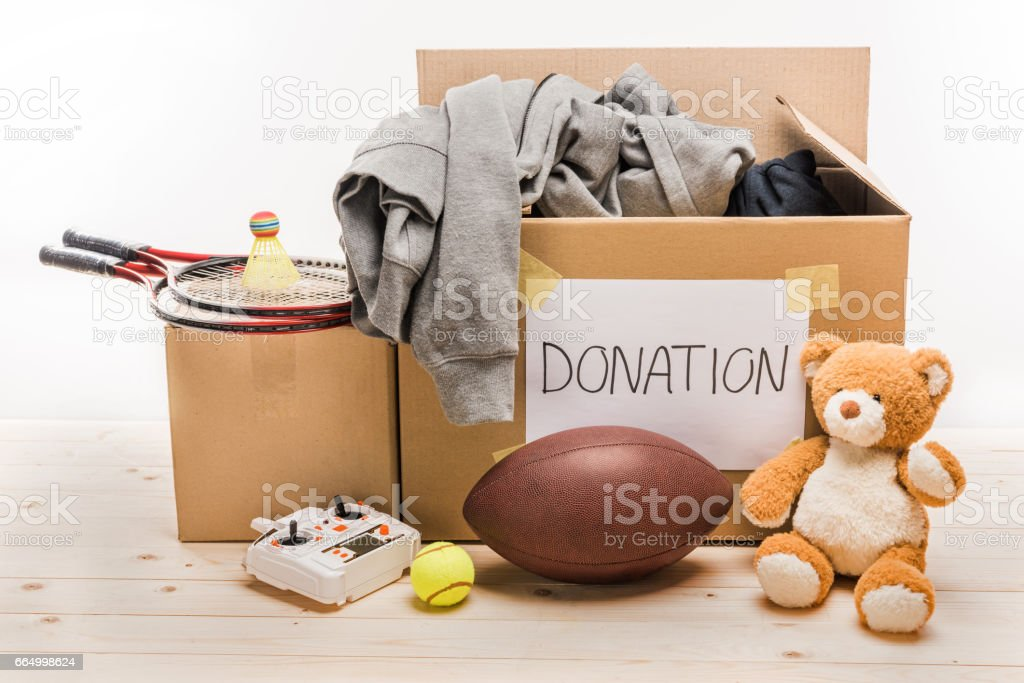 cardboard boxes with donation clothes and different objects on white, donation concept stock photo