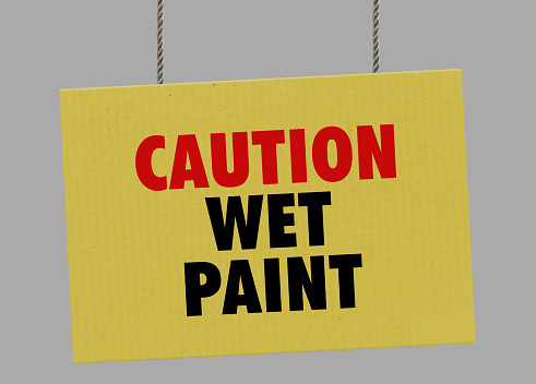 istock Cardboard caution wet paint sign hanging from ropes. Clipping path included so you can put your own background. 1047119036