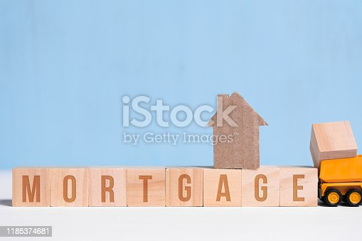 Cardboard cutout house on cubes with inscription mortgage and toy truck on blue background. Concept of construction loan, hypothec, debt, credit.