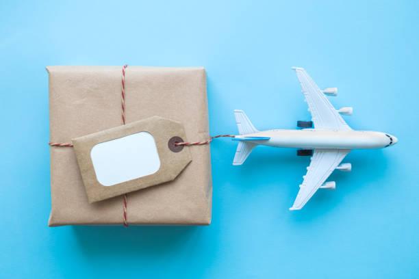 Caja de entrega de cartón con etiqueta de espacio de copia y pequeño resumen de avión en azul. - foto de stock