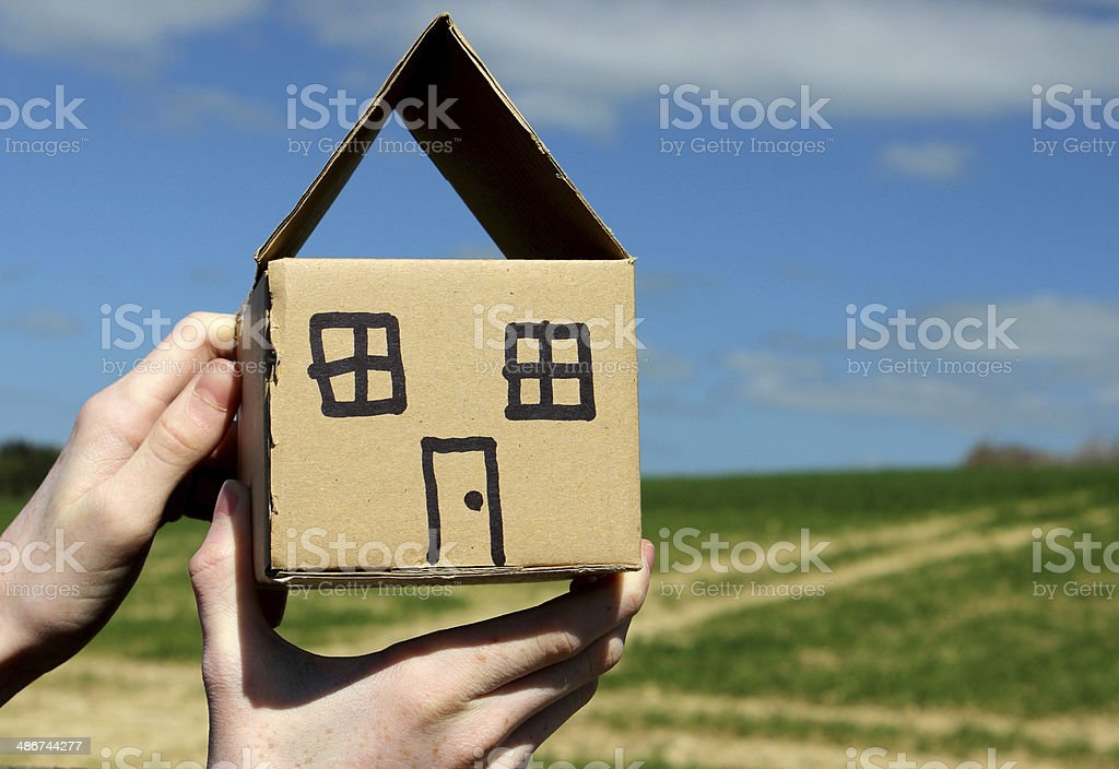 Cardboard dolls house being held in hands against sky stock photo