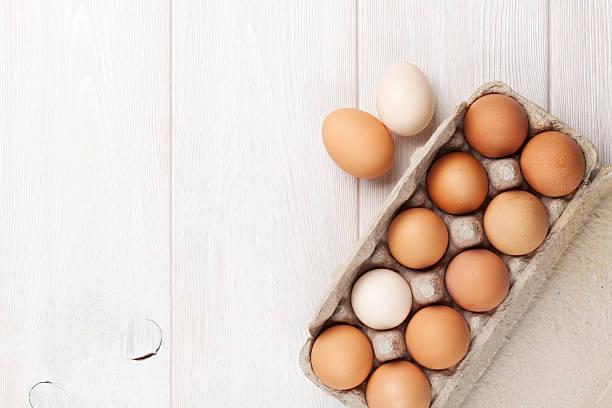 karton ei box auf holztisch - eierverpackung stock-fotos und bilder