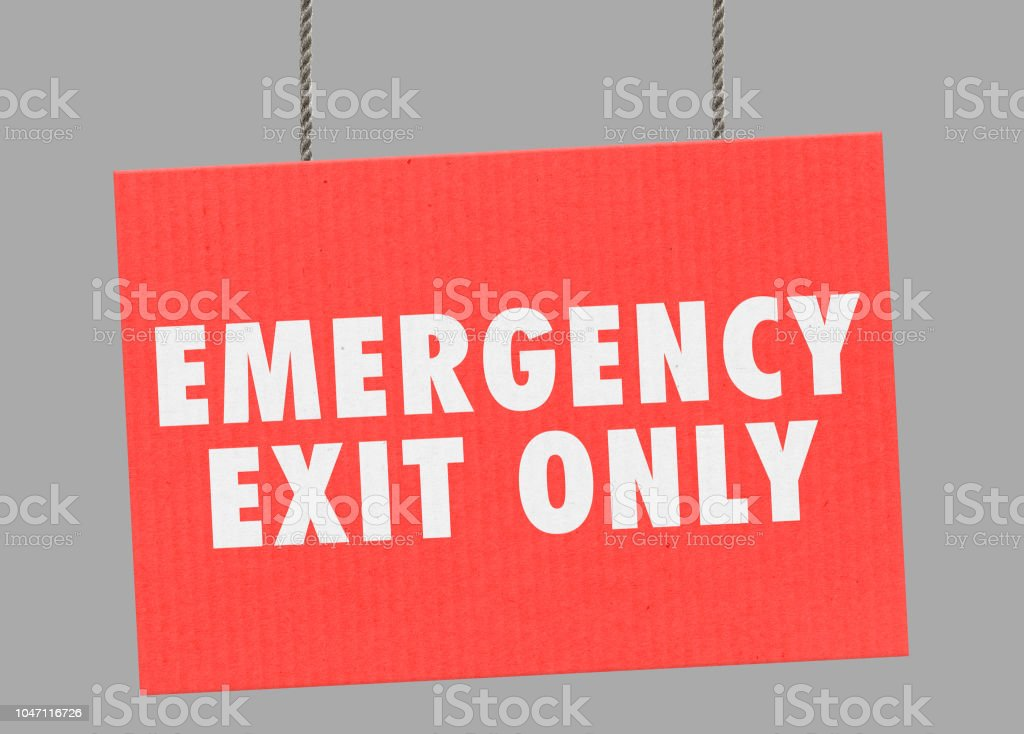 Cardboard emergency exit only sign hanging from ropes. Clipping path included so you can put your own background. stock photo