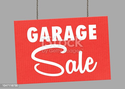 istock Cardboard garage sale sign hanging from ropes. Clipping path included so you can put your own background. 1047116730