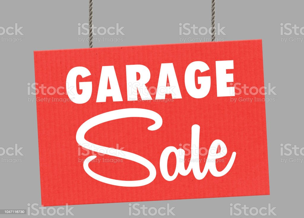 Cardboard garage sale sign hanging from ropes. Clipping path included so you can put your own background. stock photo
