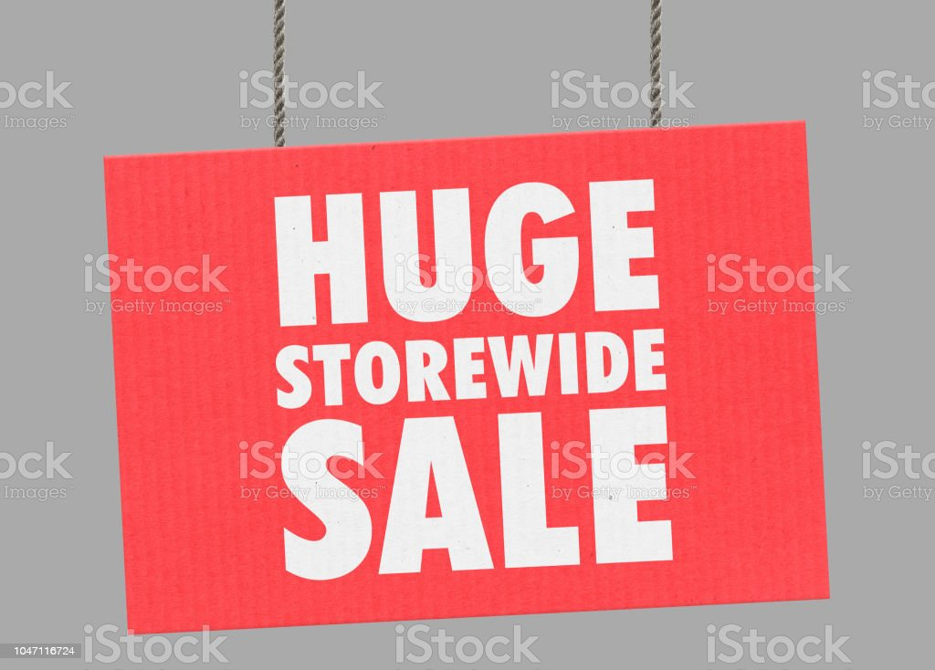Cardboard huge storewide sale sign hanging from ropes. Clipping path included so you can put your own background. stock photo