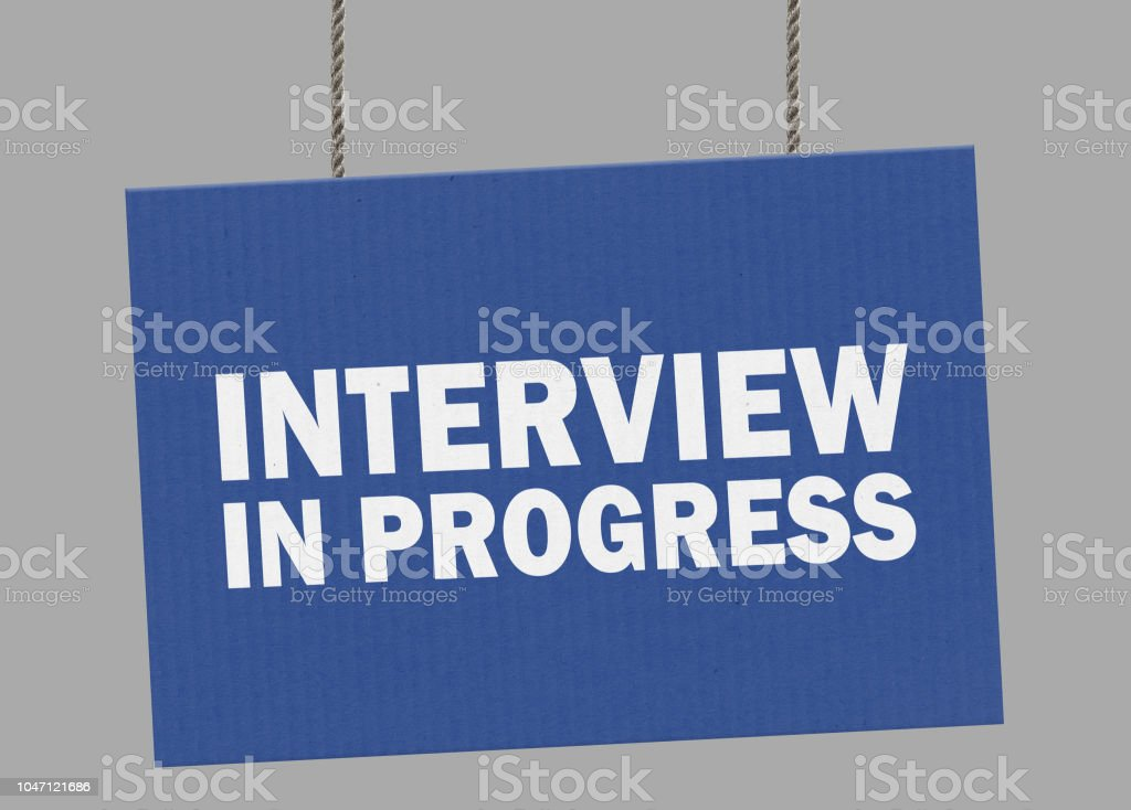 Cardboard interview in progress sign hanging from ropes. Clipping path included so you can put your own background. stock photo