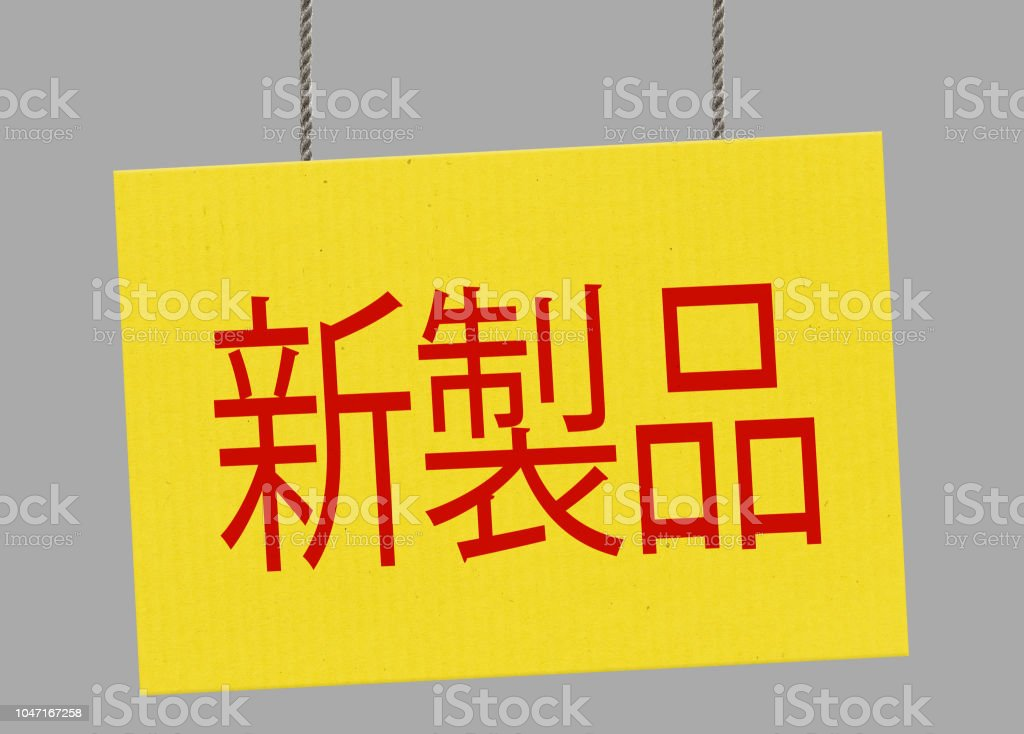 Cardboard new product japanese sign hanging from ropes. Clipping path included so you can put your own background. stock photo