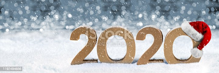 cardboard number 2020 with red white santa claus hat in snow in front of bright silver bokeh wooden background. Christmas and new year´s eve holiday panorama concept.