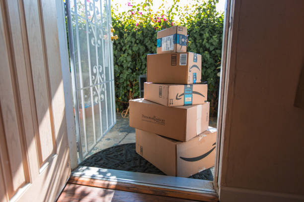 Cardboard package delivery at front door Los Angeles CA, November 11/22/2017: Image of an Amazon packages. Amazon is an online company and is the largest retailer in the world. Cardboard package delivery at front door during the holiday season. shipping package parcel box on wooden floor with protection paper inside. Amazon.com went online in 1995 and is now the largest online retailer in the world. brand name stock pictures, royalty-free photos & images