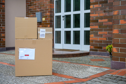 Stacked packages laying on the floor in front of the doorstep of a house.