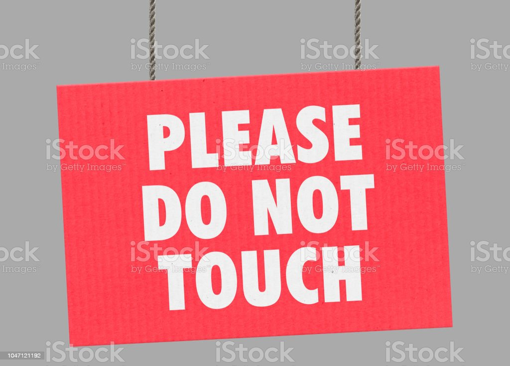 Cardboard please do not touch sign hanging from ropes. Clipping path included so you can put your own background. stock photo