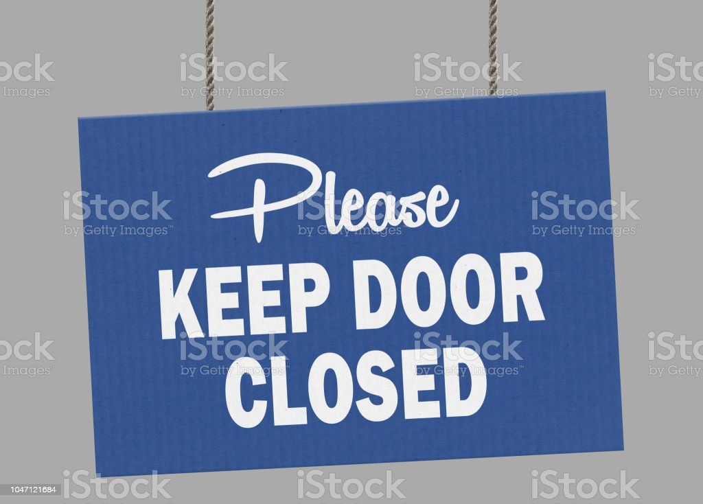 Cardboard please keep door closed sign hanging from ropes. Clipping path included so you can put your own background. stock photo