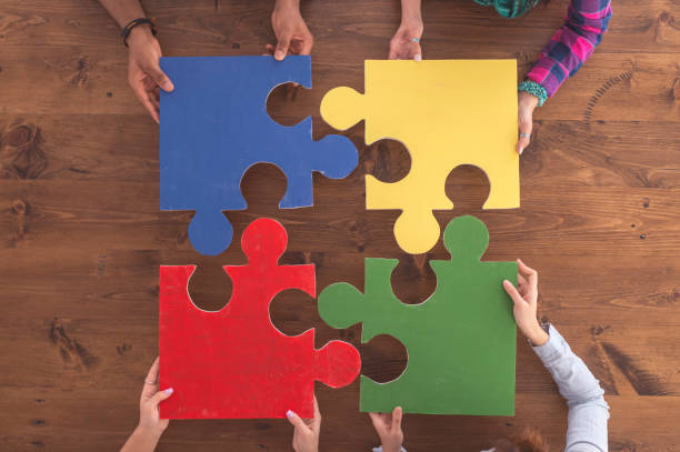 Cardboard puzzle pieces Overhead view of four large puzzle pieces that fit together into a square. There are four students who are each holding a piece. The pieces are blue, yellow, red, green. The background is a wooden table. four people stock pictures, royalty-free photos & images