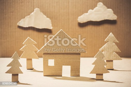 A simple diorama of a environmentally friendly recycling concept, depicting a house in a natural setting, surrounded by trees made entirely of brown cardboard paper.  Horizontal image.