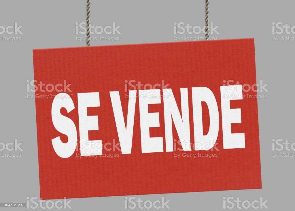Cardboard se vende  sign hanging from ropes. Clipping path included so you can put your own background. stock photo