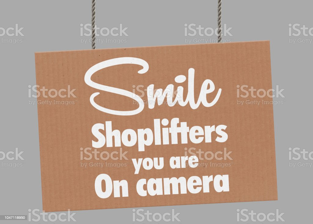 Cardboard smile shoplifters you are on camera sign hanging from ropes. Clipping path included so you can put your own background. stock photo