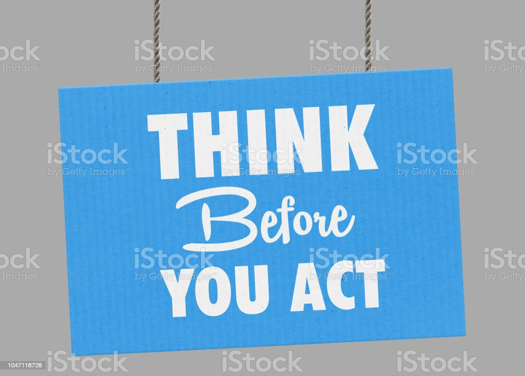 Cardboard think before you act sign hanging from ropes. Clipping path included so you can put your own background. stock photo