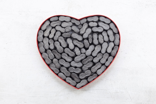 Cardbox in form of heart with black  Packing peanuts  bubbly plastic protective granules Styrofoam chips Background. love or valentine day concept