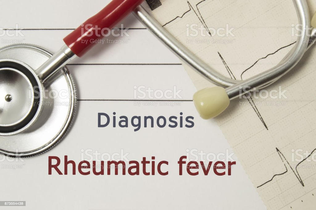 Cardiac diagnosis of Rheumatic fever. On doctor workplace are red stethoscope, printed on paper ECG line and a pen close up lying on medical handbook, which indicated diagnosis of Rheumatic fever stock photo