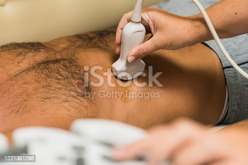 Doctor conducting ultrasound examination of patient's abdomen in clinic