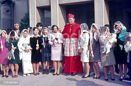 Tokyo, Honshu, Japan, 1968. A cardinal with a group of Japanese Catholic women in front of their church.