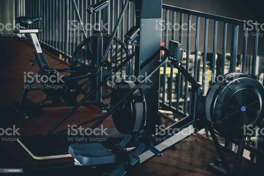 Side view of rowing machine, cable machine and air bike in an empty...