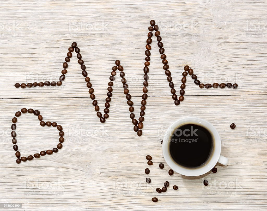 cardiogram laid out coffee beans with cup of coffee stock photo