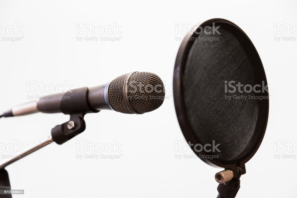 Cardioid condenser microphone and pop filter on a gray background. Home recording Studio. stock photo
