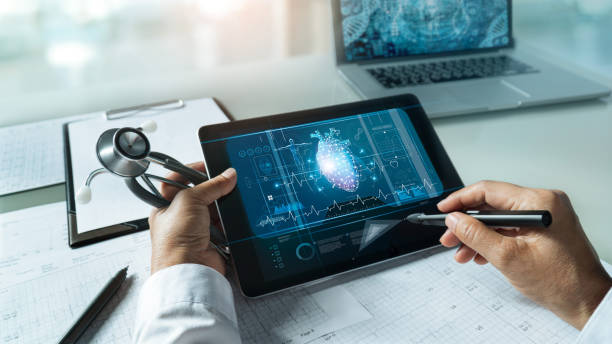 Cardiologist doctor with stethoscope. Analyzing and touching medical network connection on tablet with modern virtual screen networking interface. Medical technology and patient concept stock photo