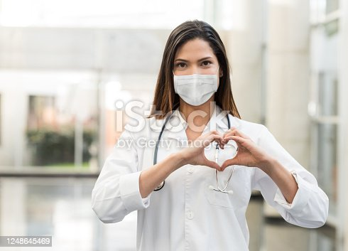 Portrait of a female cardiologist working at the hospital during the COVID-19 pandemic wearing a facemask and making a heart shape with her hands