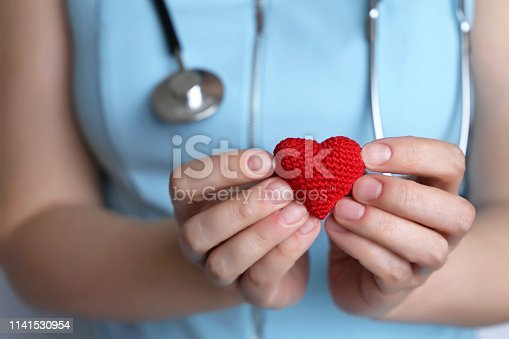 istock Cardiology and health care, woman doctor holding red knitted heart in hands 1141530954
