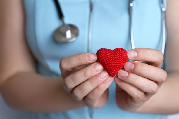 cardiology and health care, woman doctor holding red knitted heart in hands - personale sanitario foto e immagini stock