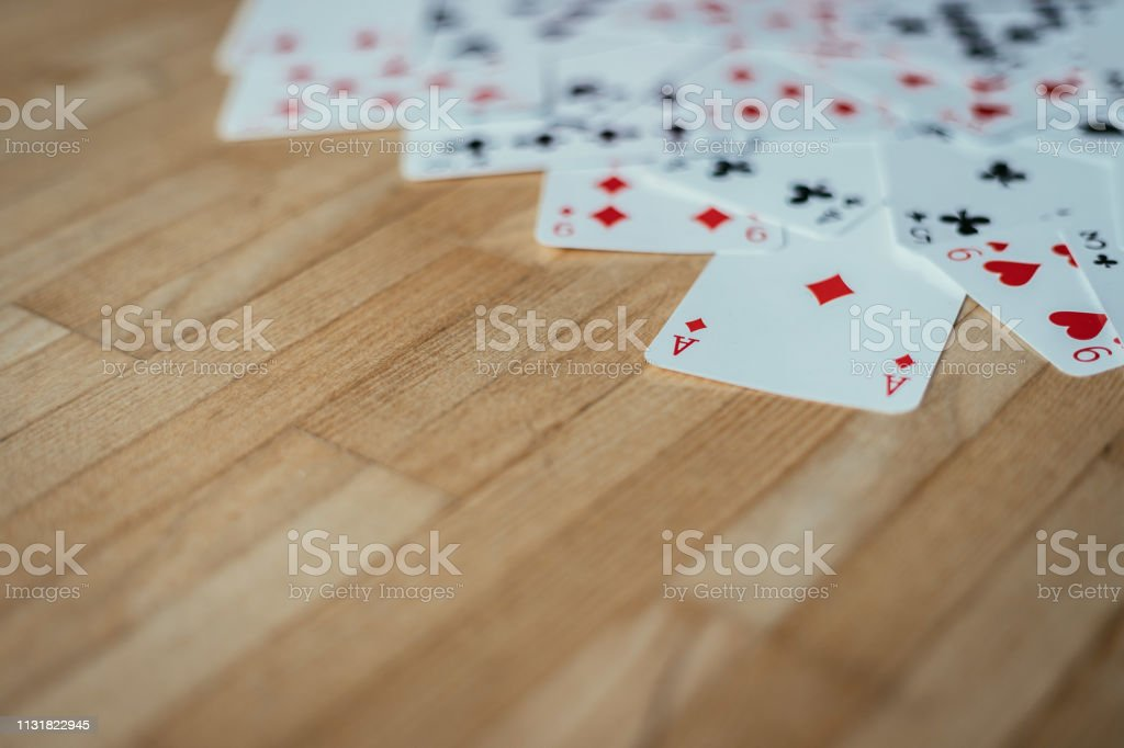 Gaming cards are lying on wood table. Playing cards at home, copy...