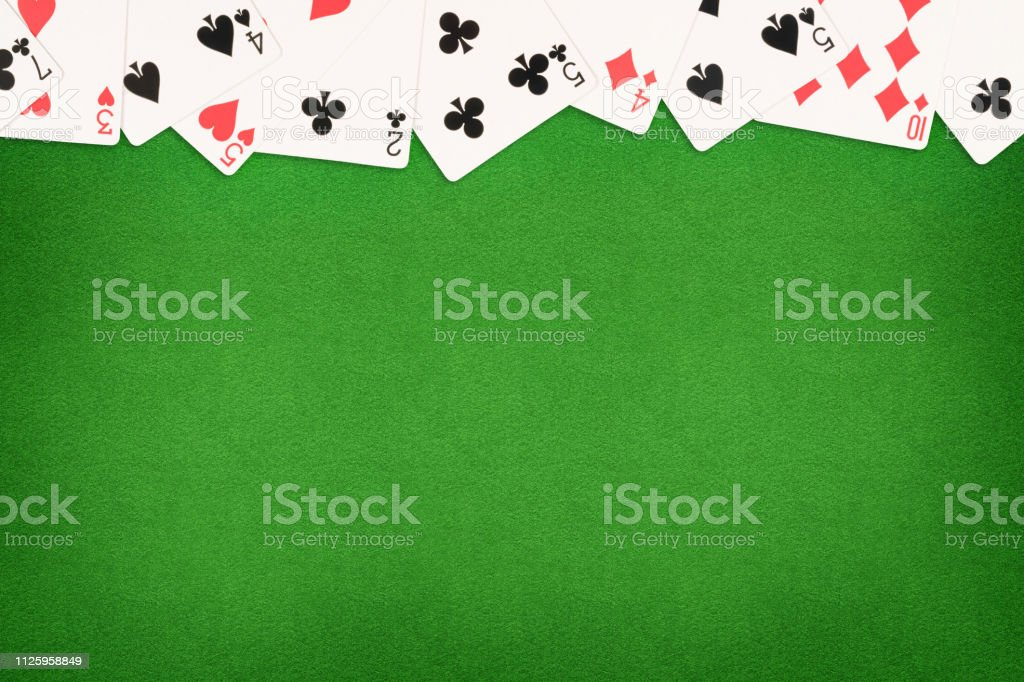 Cards on green felt casino table background. Template with copy space...