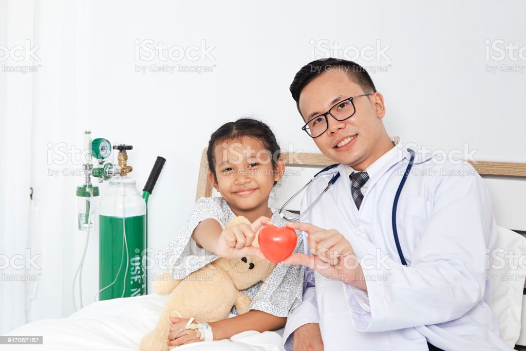Care, Asian doctor with stethoscope holding red heart and kid girl in...