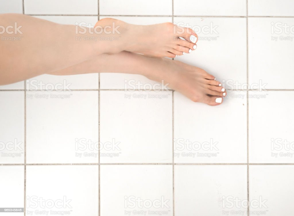 Care for beautiful woman legs on the floor from tile zbiór zdjęć royalty-free