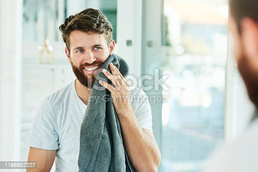 Cropped shot of a young man drying his beard with a towel
