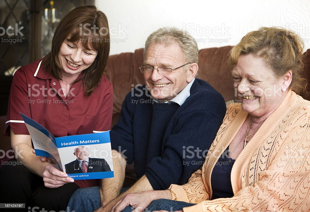 Care nurse explaining healthcare options to a senior couple royalty-free stock photo