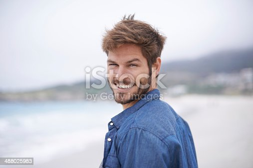 Shot of a young man enjoying a day at the beach