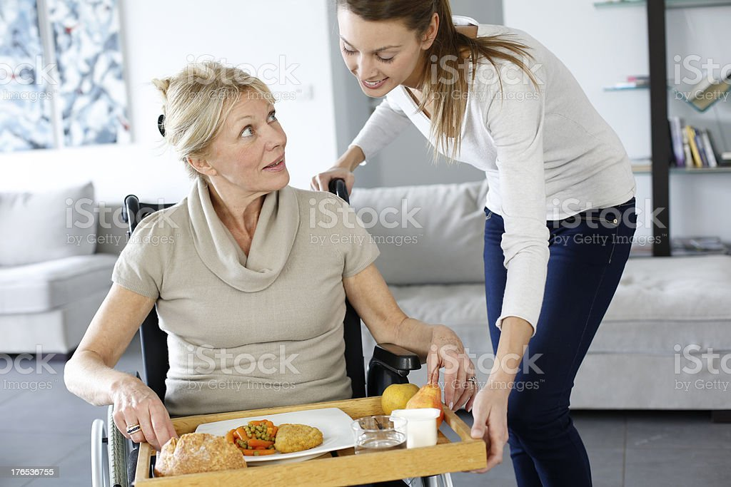Care woman giving lunch at  an old lady royalty-free stock photo