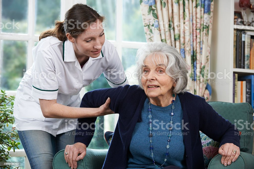 Care Worker Helping Senior Woman To Get Up stock photo