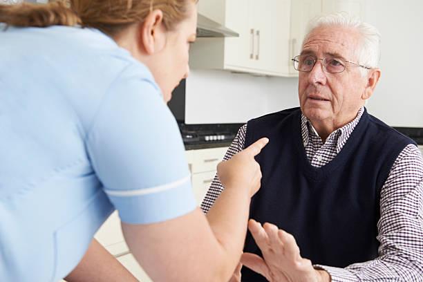 Los malos tratos inflingidos hombre trabajador de cuidado de ancianos - foto de stock