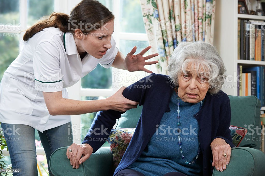 Care Worker Mistreating Senior Woman At Home stock photo